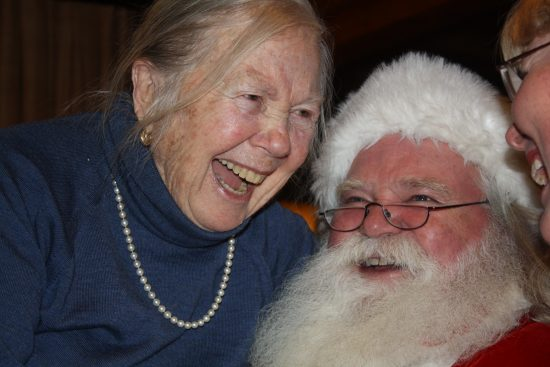 Marjorie Kade, long time guest, laughs with Santa
