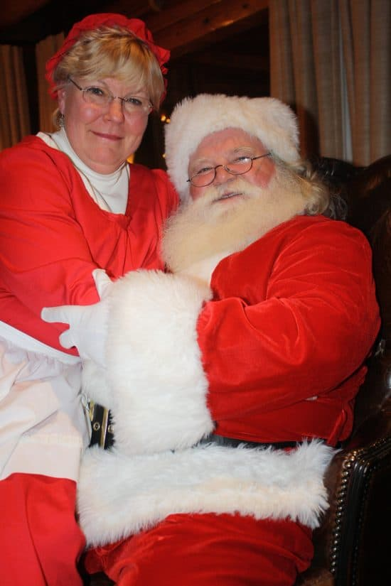 Mrs. Clause sits on Santa's lap for a picture at the end of the evening.
