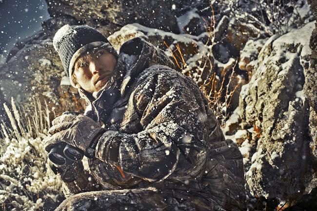Paul poses in camo, binoculars ready, as snow falls around him.