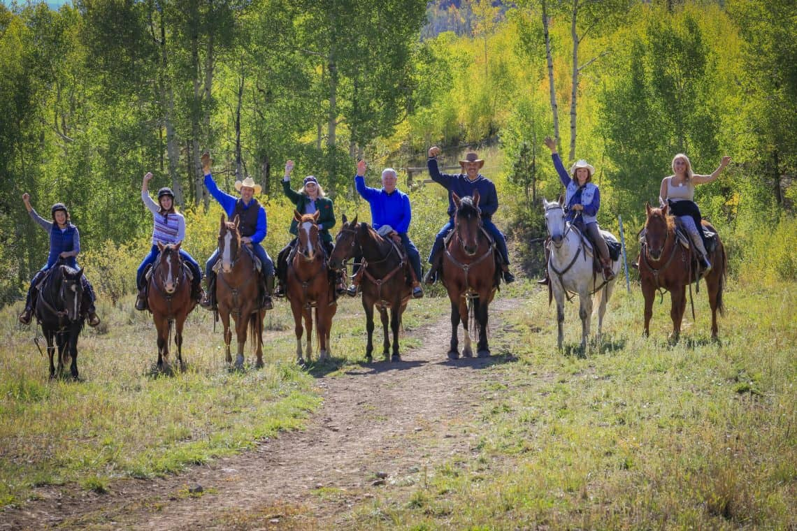 team building group waving on horses