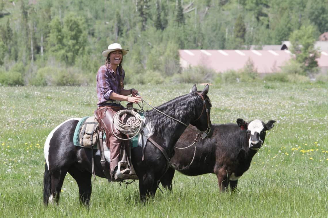 girl riding horse next to cow