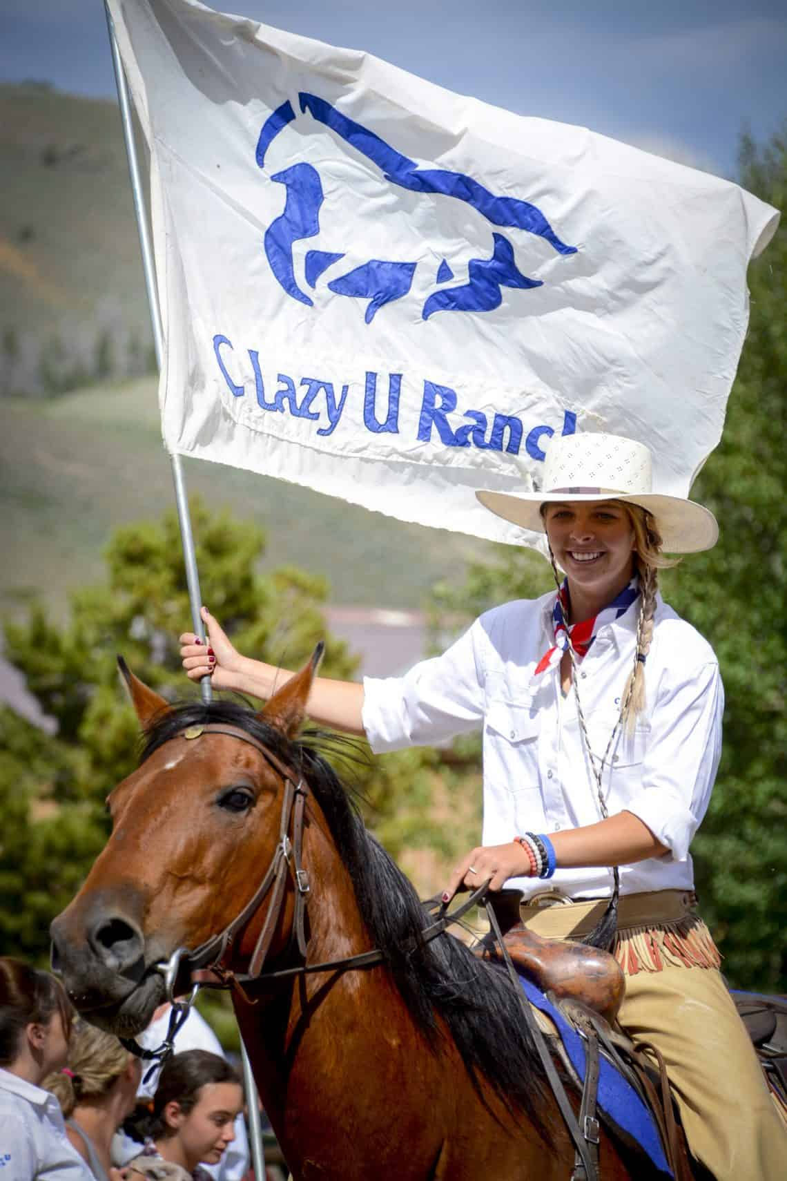 c lazy u ranch girl holding flag on horse