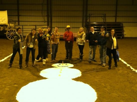 11 horseshoe players stand around a giant snowman made of flour in the indoor arena during the first annual Christmas Horseshoe Tournament