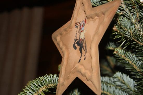 A ranch style Christmas ornament hangs from the main tree in the lodge living room.