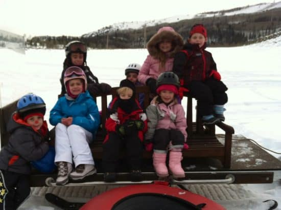 8 Kids sit on a sleigh being pulled by a snowmobile, heading out to go downhill tubing!