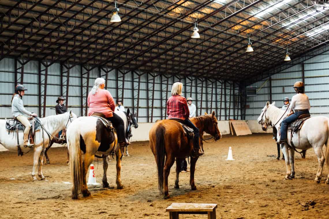 women on horses inside barn