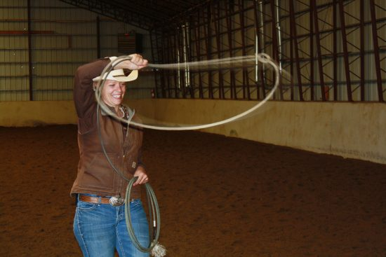 One of our brown shirts (wranglers), Tami, practicing her roping swing in the C Lazy U Ranch indoor arena