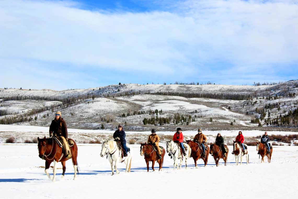 group of people horse back riding in the snow