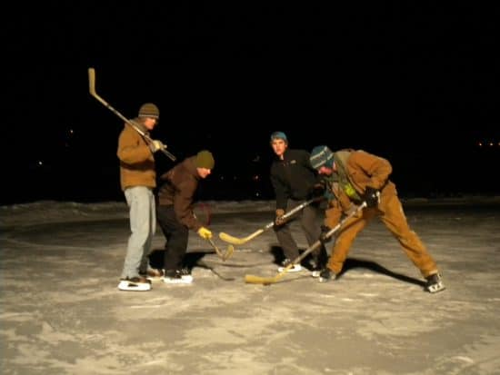 4 C Lazy U Ranch boys play hockey at night, on the freshly zambonied pond