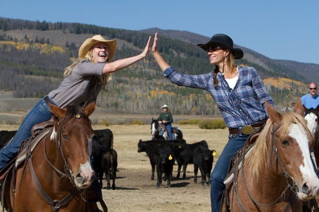 2 ladies on horses high-fiving