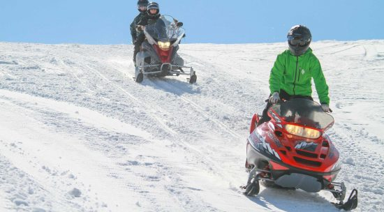Snowmobiling in the winter sunshine at luxury dude ranch