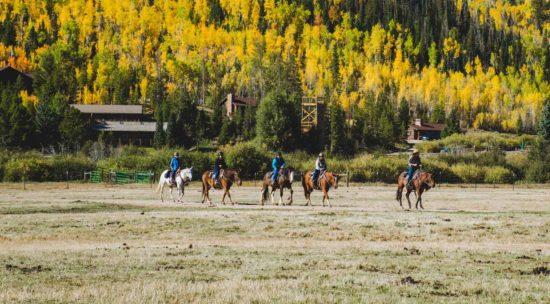 riding horses across a field in the fall at C Lazy U Ranch
