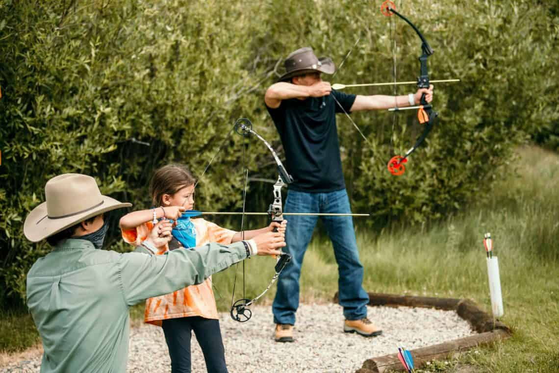 A father and daughter enjoy archery at the ranch