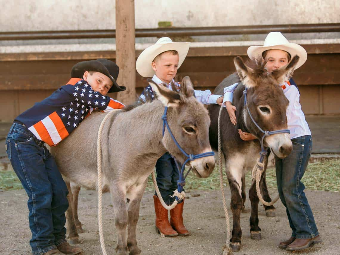 3 boys pose for a photograph with the ranch mascots: Petely and Tilly.