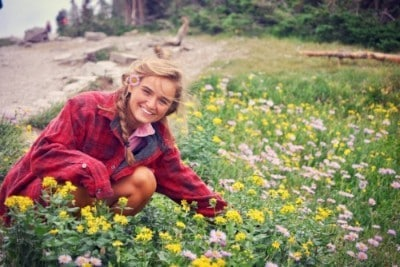 Anna Taylor posing by flowers