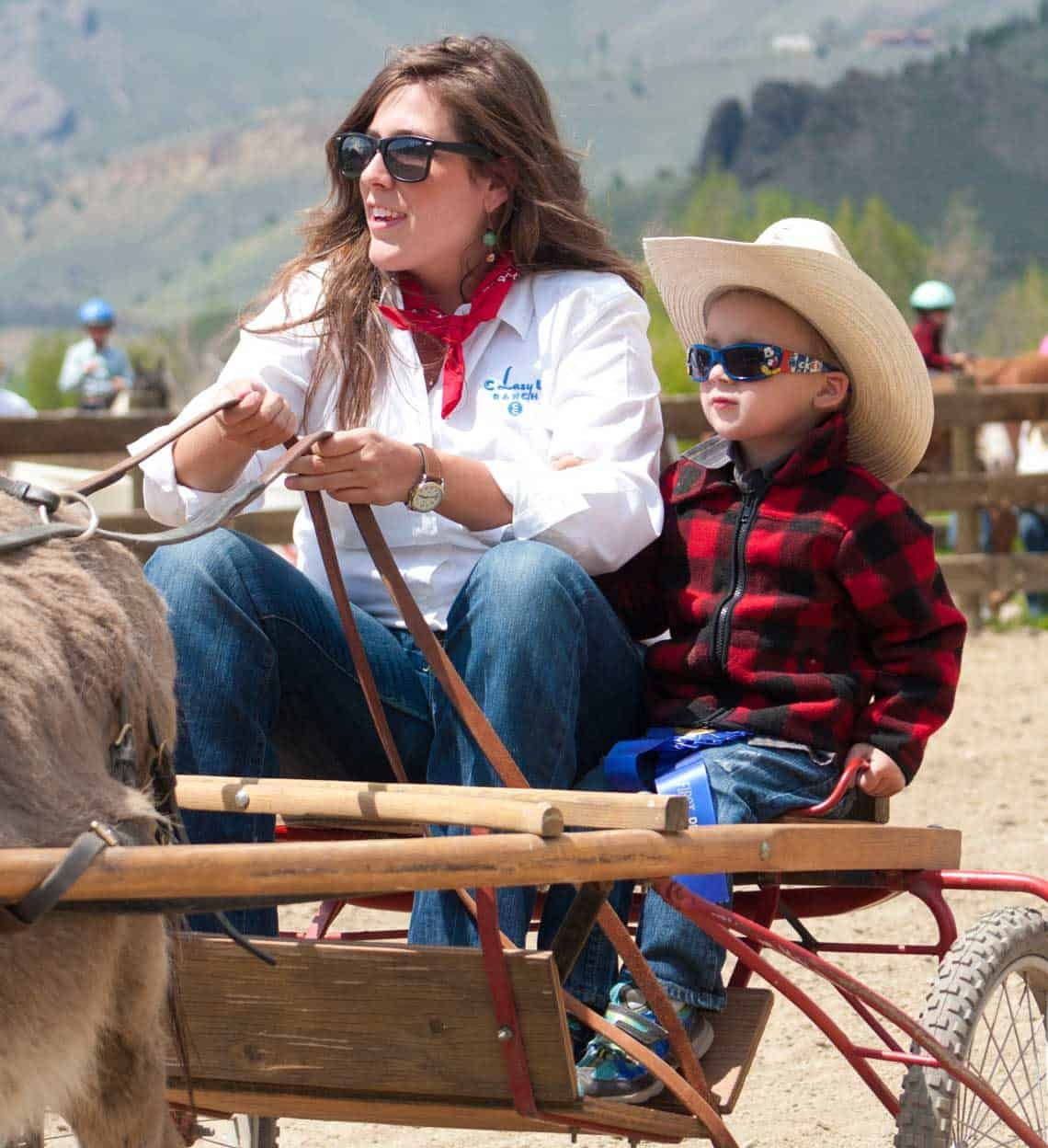 A wee guest enjoys a donkey cart ride during his family's spring vacation at C Lazy U
