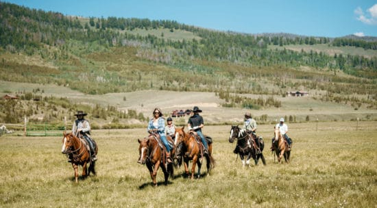 A family enjoys a trail ride in late summer at C Lazy U