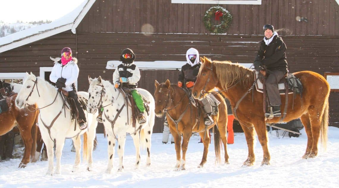 A family sets out on a horseback riding during the holidays at C Lazy U Ranch