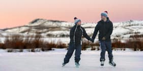 A couple ice skating while on their romantic getaway