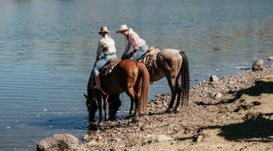 Two women on horses let the horses drink from the lake