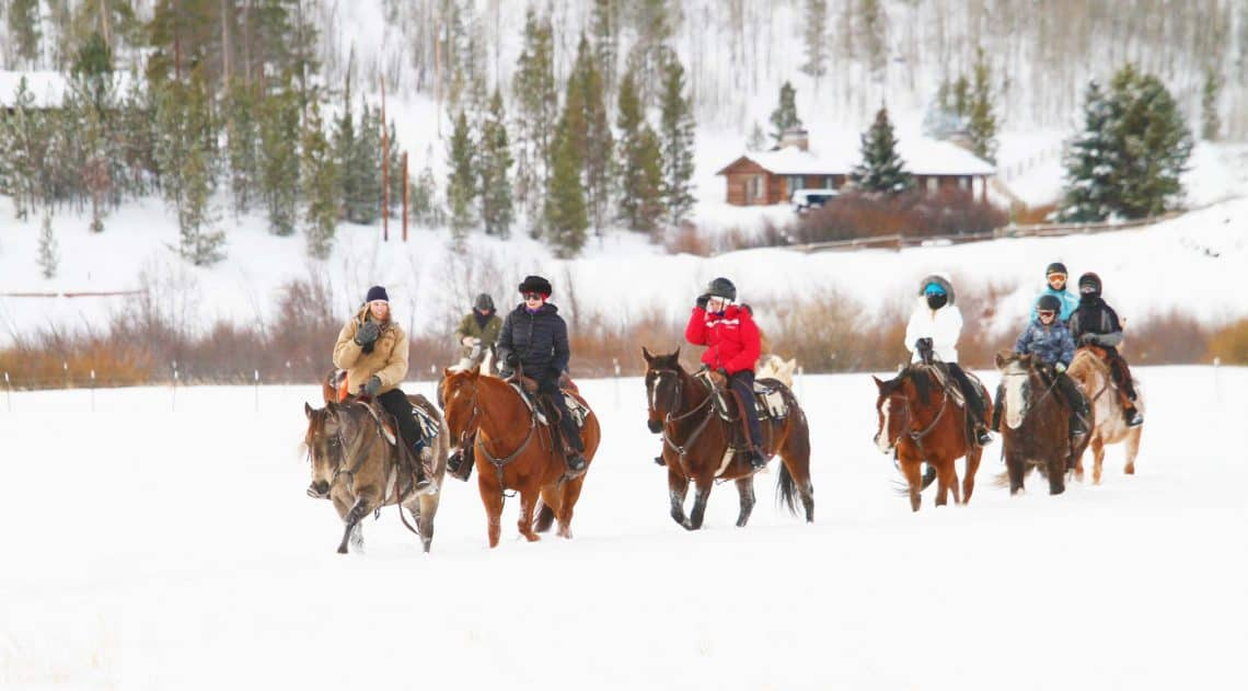 Guests riding horses in winter time at the C Lazy U ranch