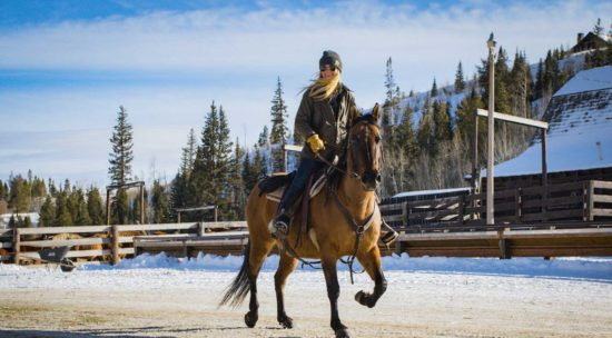 A rider trots her horse down the main road of the ranch