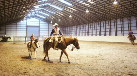 A child rides the pony in the indoor arena during her winter horseback riding vacation