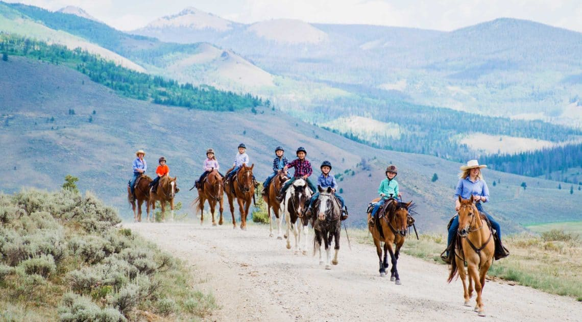 Children in the kids program at C Lazy U ride out on a trail ride with their counselors.