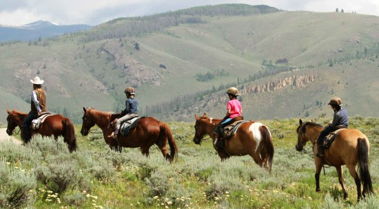 Kids out on a trail ride in the mountains during their vacation at C Lazy U in Colorado