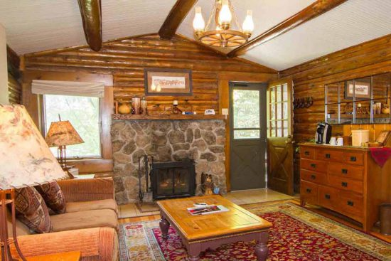 Warm up by the fireplace after a long day on your winter vacation in Colorado. Nearly all of our cabins have one.