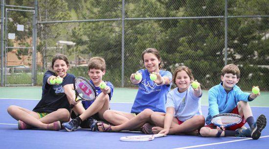 Kid sitting on tennis court holding tennis balls