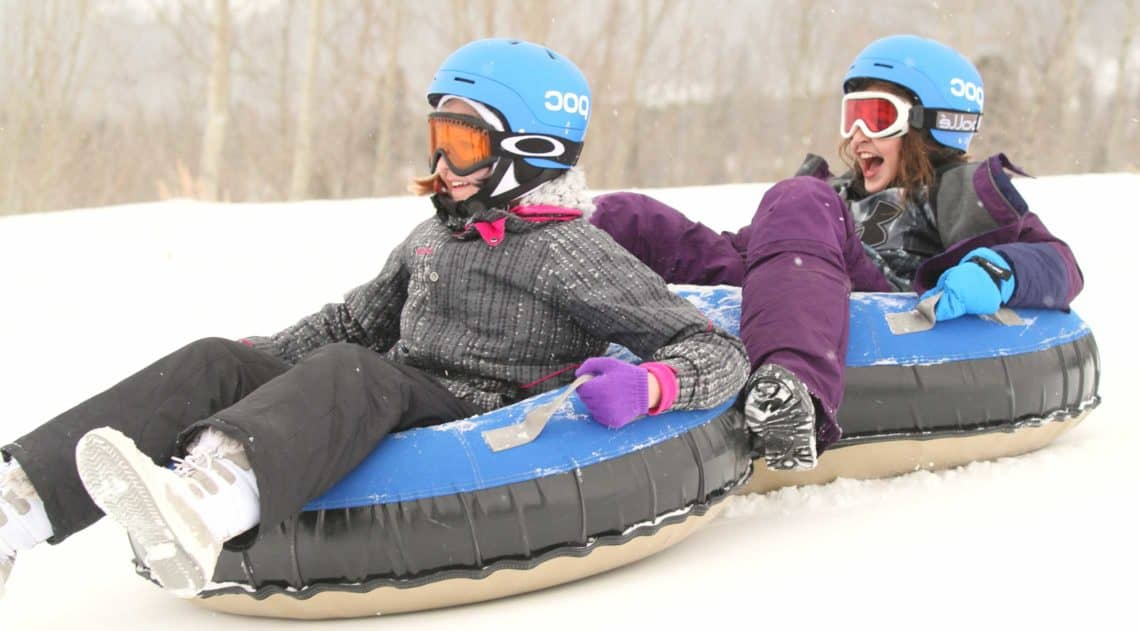 Two girls snowtubing during a winter getaway vacation at C Lazy U