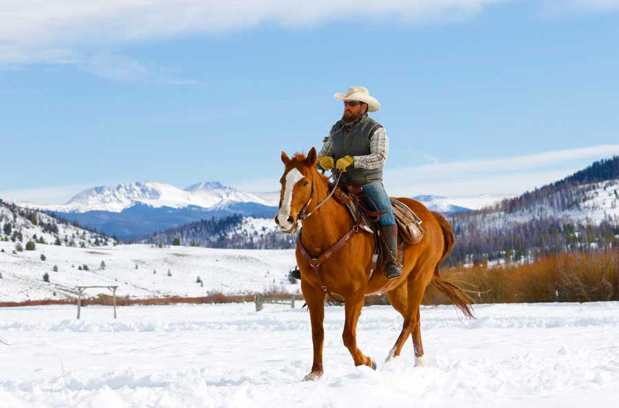 A dude ranch guest rides his horse through the snow.