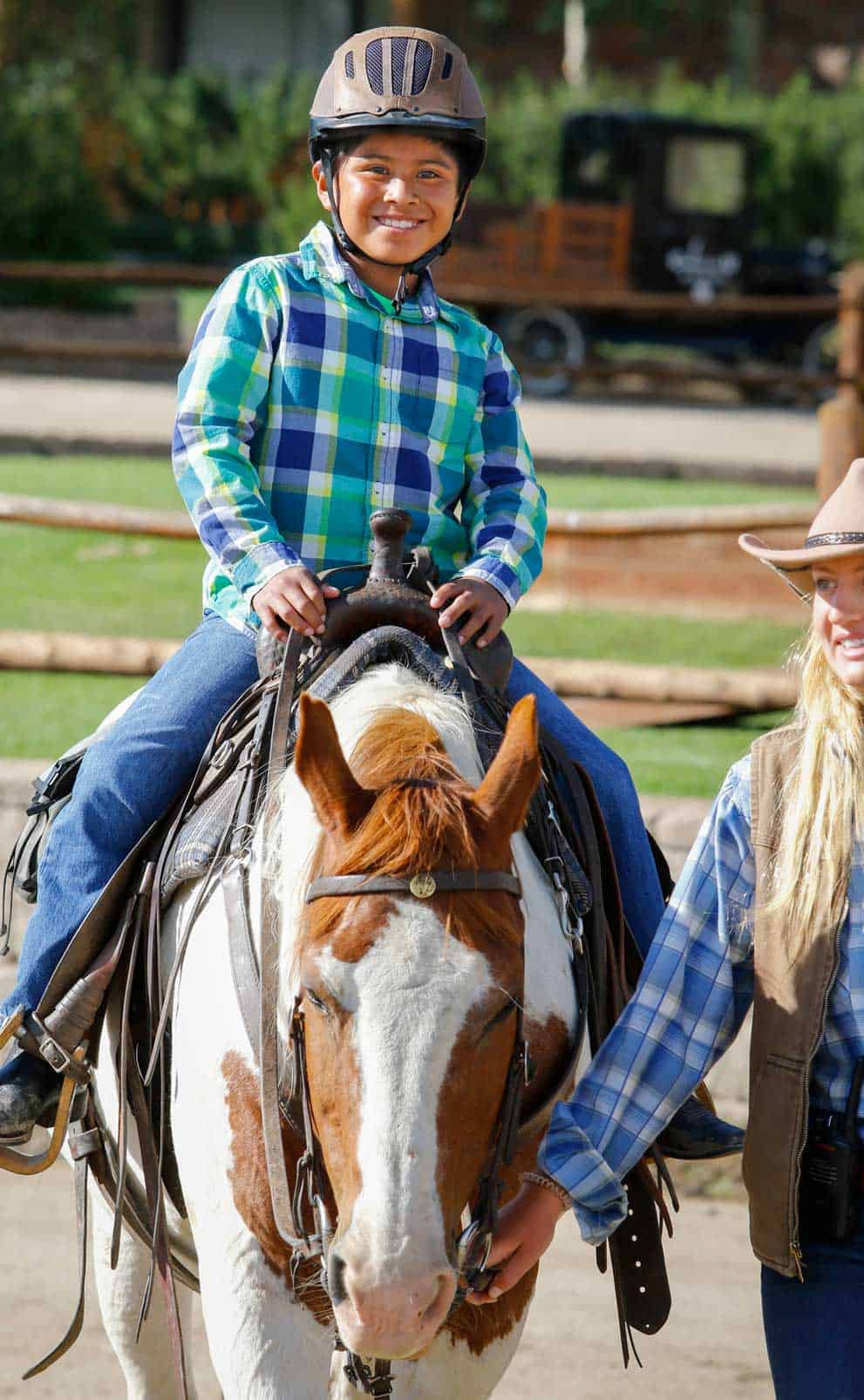 A young boy grins from ear to ear during his pony ride